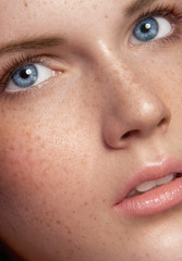 Close up beauty portrait of young girl with a lot of freckles
