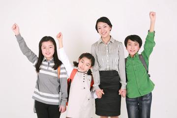 웃으며 서있는 아시안 여성과 세 명의 어린이