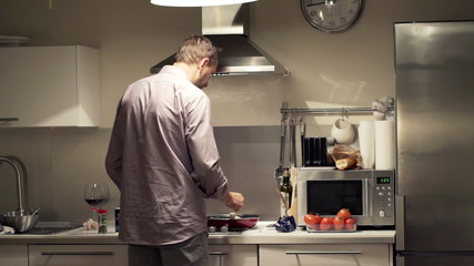 Young man cooking and adding seasoning in kitchen at home