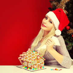 Girl making gingerbread house. Woman with Santa Hat