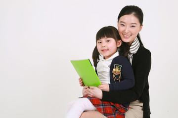 여자 아이에게 책 읽어주는 여선생님