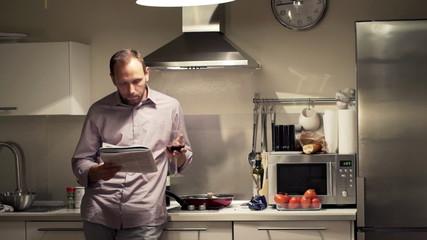 man reading magazine, drinking wine in kitchen at night
