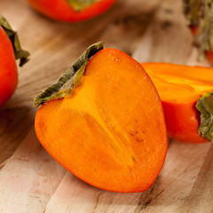 Delicious orange persimmons on wooden table. Selective focus.