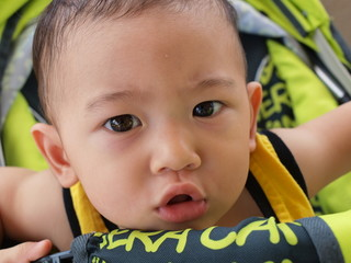 Asian baby with doubtful look on his face in sitting stroller.