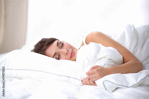 Beautiful girl sleeps in the bedroom, lying on bed - 74875835