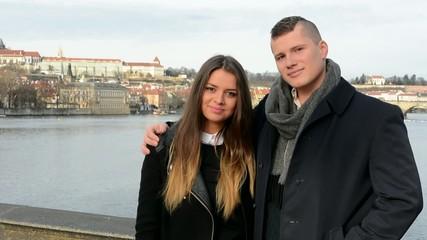young happy couple smile on the bridge - city