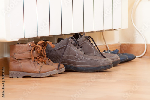 pairs of shoes on   radiator - 74878826