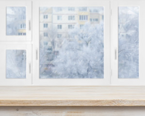 Wooden table surface over frosty window background
