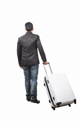 rear view of young man and pulling belonging luggage walking to