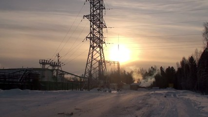 Production site with a high-voltage tower at winter.