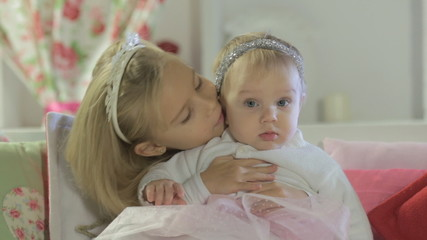 Beautiful little girl sitting with her little sister on the