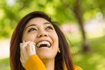 Cheerful woman using mobile phone in park
