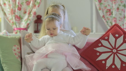 Two little sisters in the beautiful New Year headband  sit on