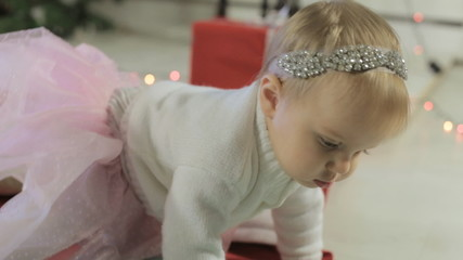 Charming toddler crawling near decorated Christmas tree