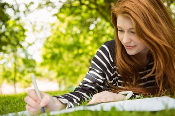 Female student doing homework in park