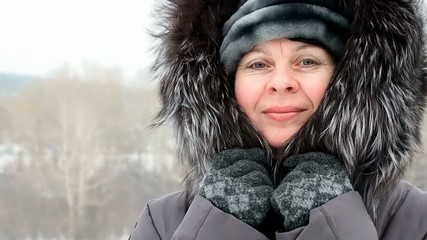 Woman wrapped in a fur collar because of cold