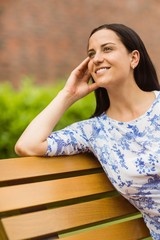Happy brunette sitting on bench relaxing