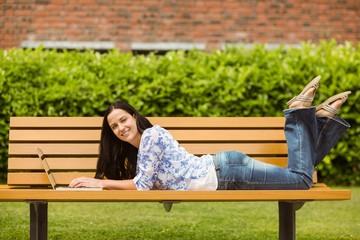 Peaceful brunette lying on bench using laptop