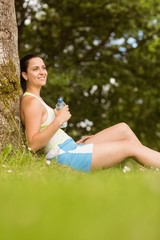 Cheerful fit brunette sitting against a tree holding a bottle