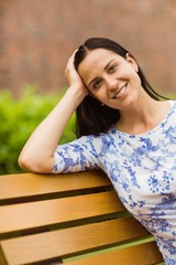 Smiling brunette sitting on bench looking at camera