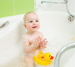 baby boy clapping hands and smiling while taking a bath