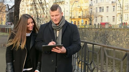 happy couple work on tablet and walk in city