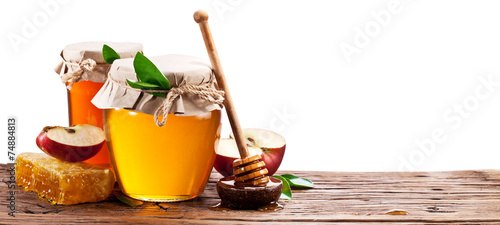 Glass can full of honey, apples and honeycombs on old wooden tab