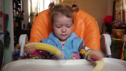 Little girl cleans and eats banana