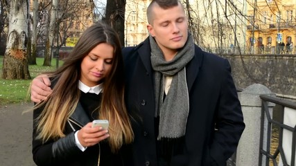 couple goes in park (city) - woman works on smartphone