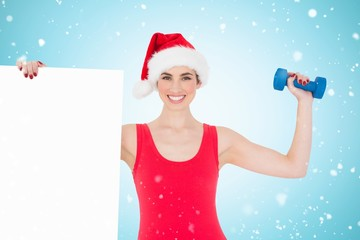 Festive fit brunette holding page and dumbbell