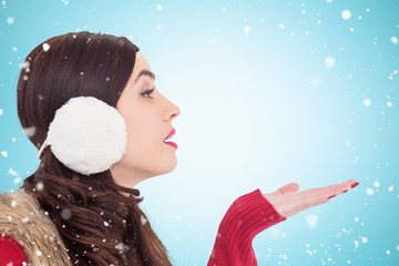 Composite image of brunette in winter clothes with hand out