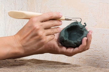 women's hands working with clay