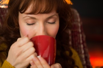Redhead with eyes closed drinking hot drink