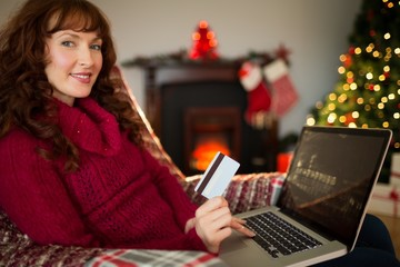 Smiling red hair shopping online with laptop