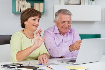 Seniors couple using a computer chatting via webcam and waving h