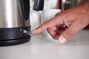 Close Up Of Man Turning On Switch To Boil Kettle