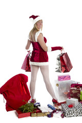Woman in Santa outfit holding Christmas presents