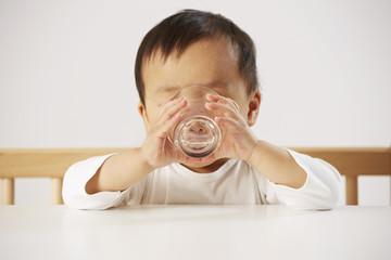 Kind trinkt Wasser aus dem Glas