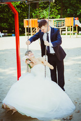 beautiful young wedding couple in park, blonde bride on swing an