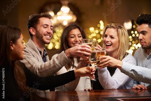 Leinwanddruck Bild Group Of Friends Enjoying Evening Drinks In Bar