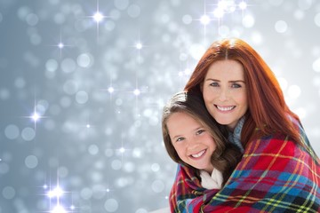 Composite image of mother and daughter under blanket