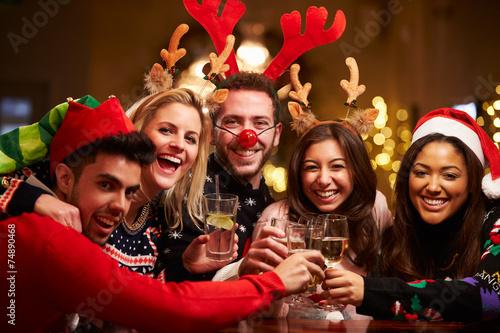 Leinwandbild Motiv Group Of Friends Enjoying Christmas Drinks In Bar