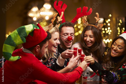 Group Of Friends Enjoying Christmas Drinks In Bar - 74890629