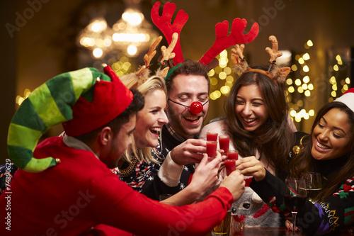 Group Of Friends Enjoying Christmas Drinks In Bar - 74890629