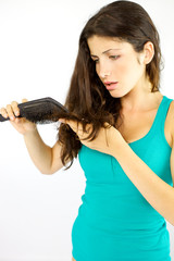 Woman seeing split ends in her long hair while brushing