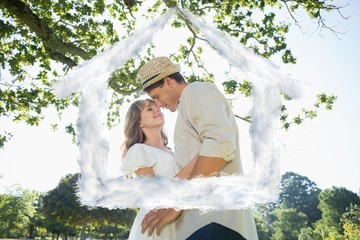 Composite image of cute couple standing in the park embracing