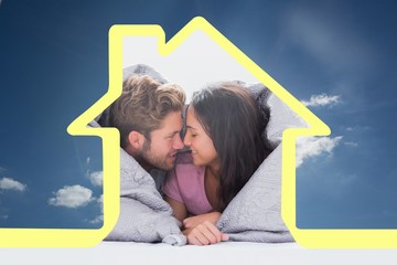 Composite image of beautiful couple wrapped in the duvet