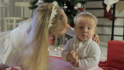 Little girl playing with her baby sister near Christmas tree