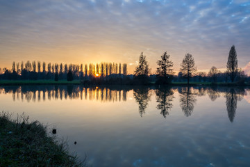 Winter sunset in the shore of a lake with clouds reflected in th