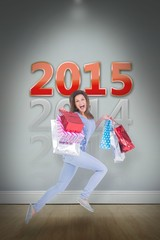 Excited brunette jumping while holding shopping bags